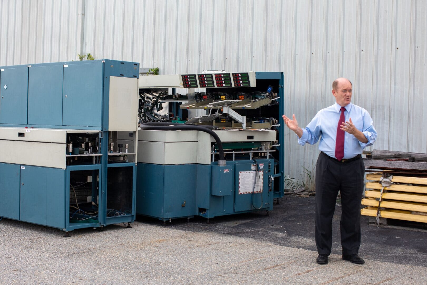 Sen. Chris Coons stands next to mail-sorting equipment left in the rain in New Castle.